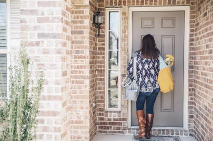 Woman opening sandy front door