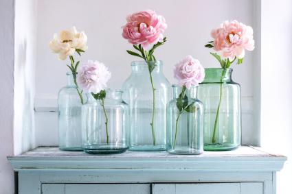 Single peonies in green glass vases