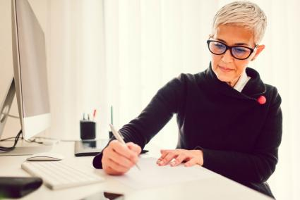 Woman taking notes at her desk