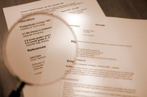 Freelancer proofreading a resume with a magnifying glass