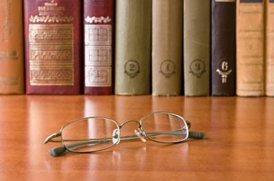 Reading glasses on table in front of research books