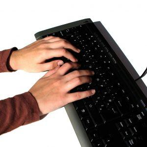 Freelance writer typing on a computer keyboard