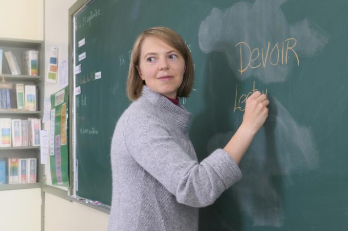 French teacher writing on chalkboard