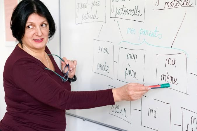 Woman teaching French at whiteboard