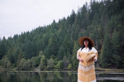 First Nations woman playing drum