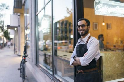 Business owner standing outside cafe