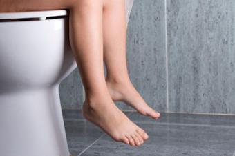 Naked person sitting on toilet