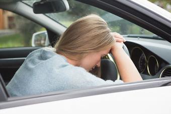 Woman asleep on steering wheel