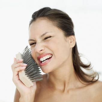 Woman brushing face with wire brush