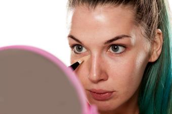 Woman applying concealer beneath her eyes