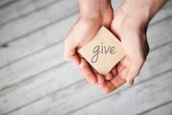 Hands hold card that says 'give'