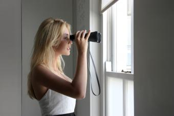 Woman looking out window with binoculars