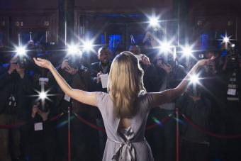 arms outstretched to paparazzi