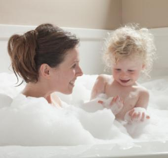 Mother and child having bubble bath