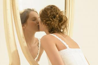 Woman kissing reflection in mirror