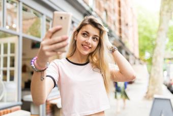 Woman taking selfie outdoors using smartphone