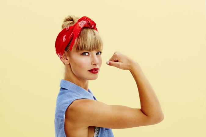 Woman posing as Rosie the Riveter