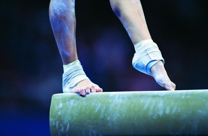 Female gymnast's feet on the balance beam