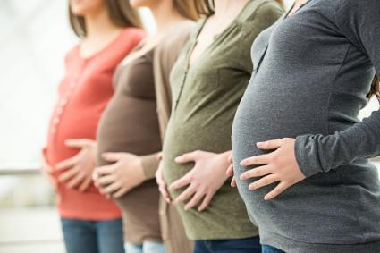 Pregnant women holding their bellies
