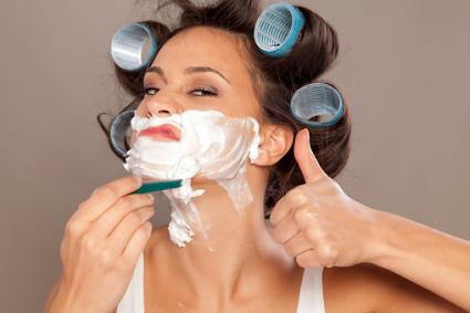 Woman in curlers shaving face