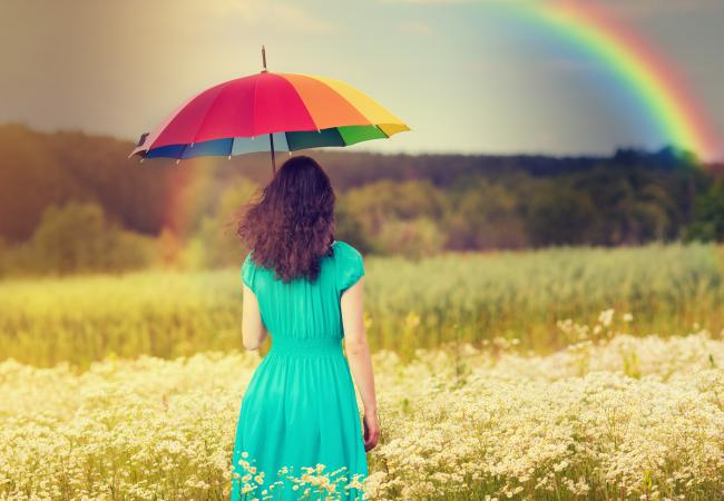 Young woman underneath rainbow