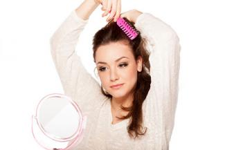 Woman taming flyaways with brush