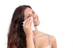 Woman blotting face with tissue