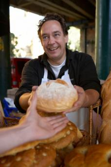 Man handing bread to customer