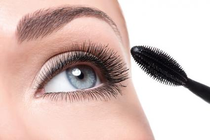 Woman applying mascara to her eyelashes