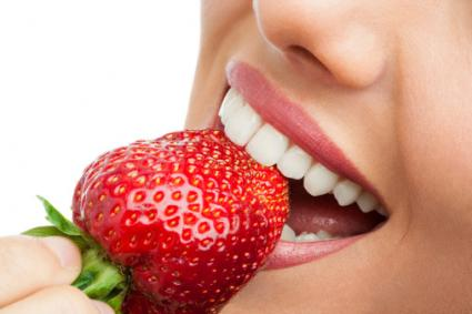 Woman biting strawberry