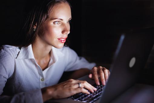 Woman using computer late at night