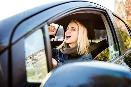 Woman driving a car singing