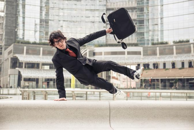 Man jumping over wall with briefcase