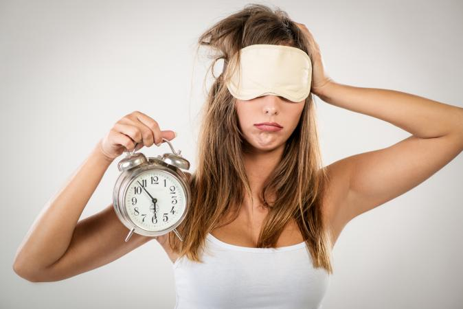 Overtired woman with clock and blindfold