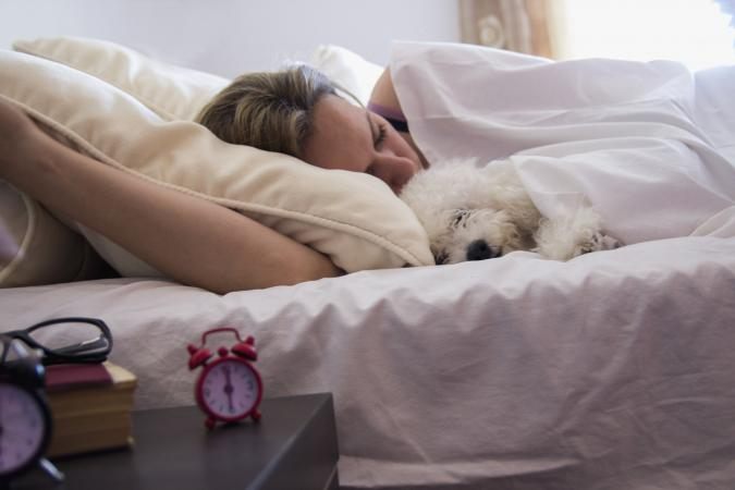 woman snuggling dog in bed