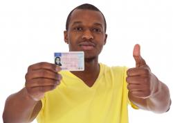 Man proudly showing drivers license