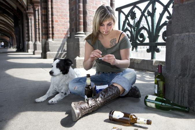 Street girl with boots and beer sitting on the cement