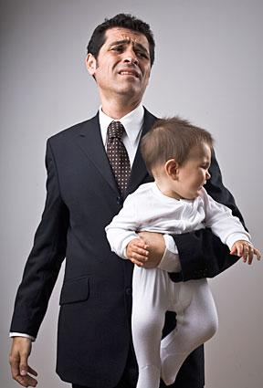 unhappy businessman holding crying baby