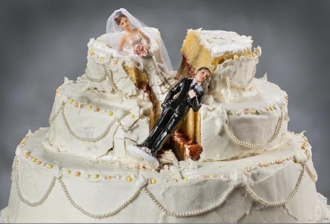 Bride and groom figurines collapsed on fallen wedding cake