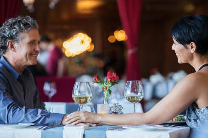 Mature couple holding hands at restaurant