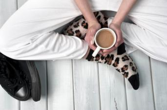 Woman on floor holding coffee mug