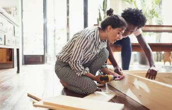 Young women assembling furniture with power drill