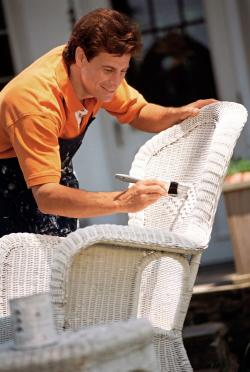 Man painting wicker chair