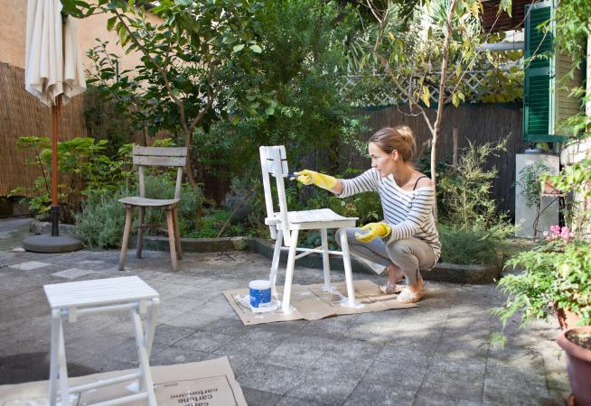 Woman painting chair on patio