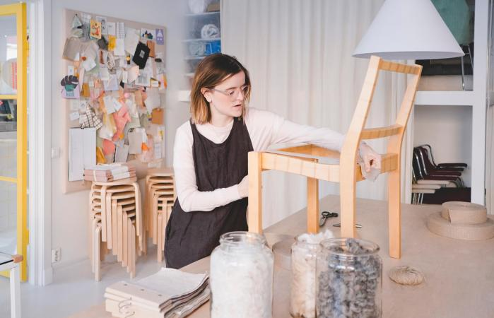 Woman working on chair in workshop