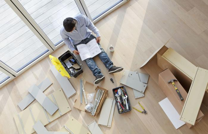 Man surrounded by flat pack furniture