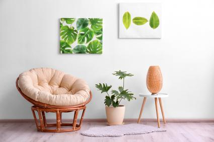 Stylish room interior with tropical leaves and papasan chair