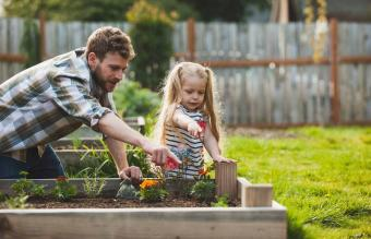 Father and daughter pointing to plant