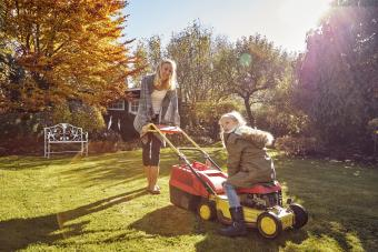 Mother with daughter in garden lawn mowing