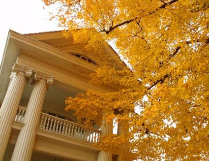 neo-classical mansion with fall foliage